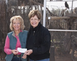 Linda Searle, Executive Director of Southwest Wildlife, accepting check from artist Linda Budge